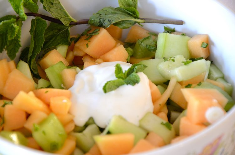 Cucumber, kiwi, canteloupe cubes in salad bowl with creamy dressing and mint garnish.