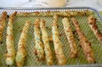 Crispy, breaded asparagus spears on an air fryer rack.