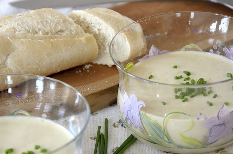 Potato leek soup garnished with fresh chives beside a baguette of fresh bread.