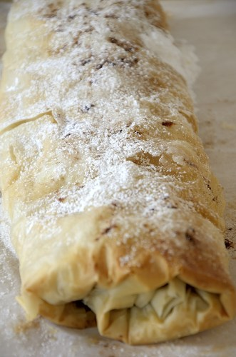 Flaky apple strudel with phyllo pastry topped with icing sugar.