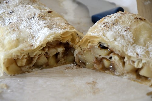 Flaky apple strudel with phyllo pastry topped with icing sugar cut open.