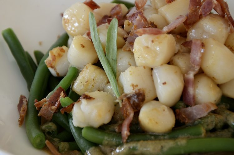 Seared scallop over green beans with bacon bits and creamy bacon dressing.