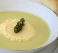 Creamy asparagus soup in a white shallow soup bowl with a Parmesan custard island in the center.