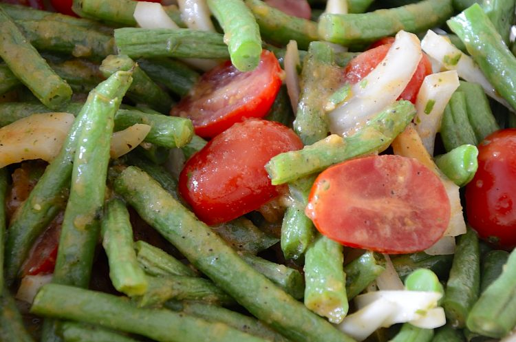 Close up of green string beans with sweet onions and cherry tomatoes in a Roasted Tomato Dressing.