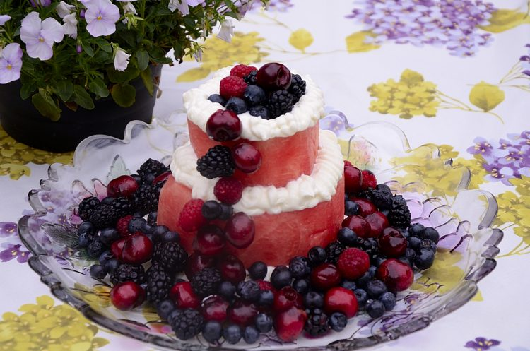 Two tiers of watermelon with cream cheese frosting piped around the edge of each layer and cherries, blackberries, blueberries and raspberries pile on the top, down one side and round the base.