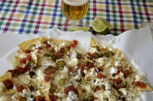 Platter of tortilla chips with cheese, salsa and cream toppings.