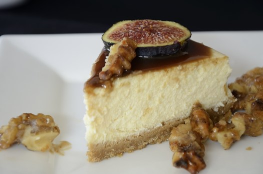 Piece of cheesecake drizzled with balsamic caramel and topped with fresh fig slices and candied walnuts.