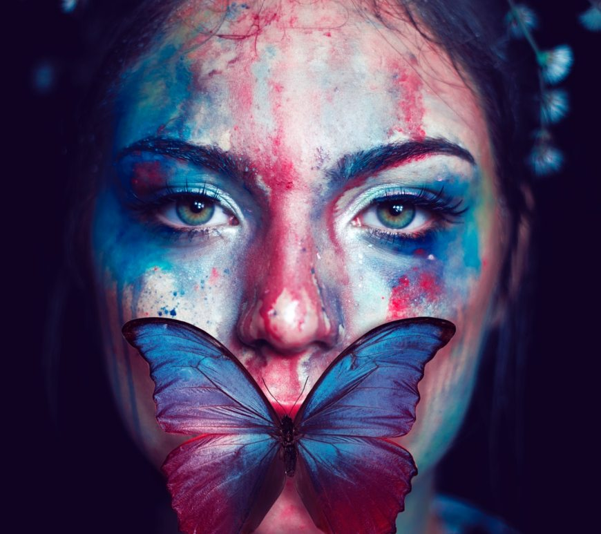 Girl in fantasy world with blue and pink butterfly across her lips and blue fairy lights in the background