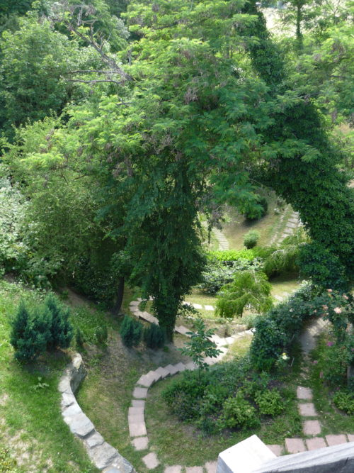 three white stone garden paths winding down into the valley of a castle garden