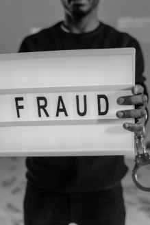 """man holding a sign that says, """"fraud"""" imposter syndrome"""