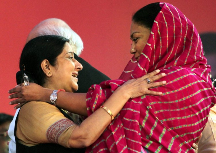 File photo of  External Affairs Minister Sushma Swaraj and Rajasthan CM Vasundhra Raje greeting  each other at a public meeting in Jaipur in October 2011. The Congress party is demanding the resignation of both BJP leaders over the Lalit Modi controversy. PTI Photo
