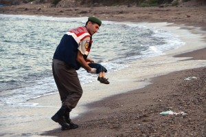 A paramilitary police officer carries the lifeless body of a migrant child after a number of migrants died when boats carrying them capsized near the Turkish resort of Bodrum. Source: DHA