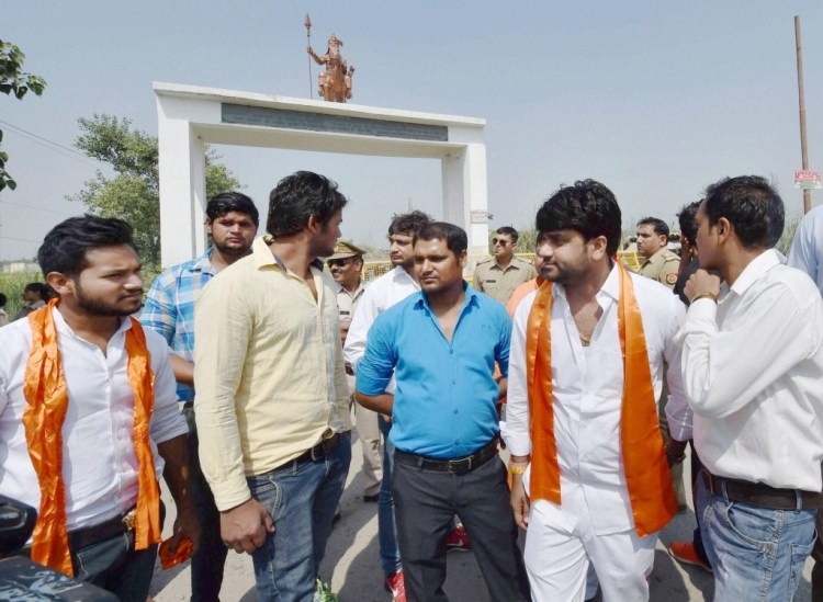 Hindu Yuva Vahini activists at the gate of Bisara Village where Mohammad Akhlaq was lynched by a mob after allegedly having beef, in Dadri on September 28. Credit: PTI Photo by Kamal Singh