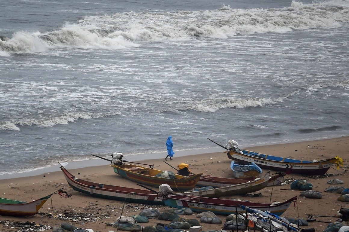 A fisherman walks near boats during heavy rain near Marina Beach in Chennai on Tuesday. Normal life has been badly affected due to incessant rains. Credit: PTI