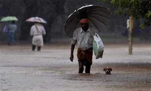 Visitors move from a flooded Government hospital after heavy rains in Chennai on Tuesday. Credit: PTI