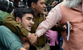 A policeman tries to save CPI leader Ameeque Jamai who was being beaten up. Credit: PTI Photo by Atul Yadav