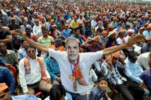 A supporter wears a mask of Narendra Modi during his election rally at Majuli in Jorhat district of Assam on Saturday. Credit: PTI