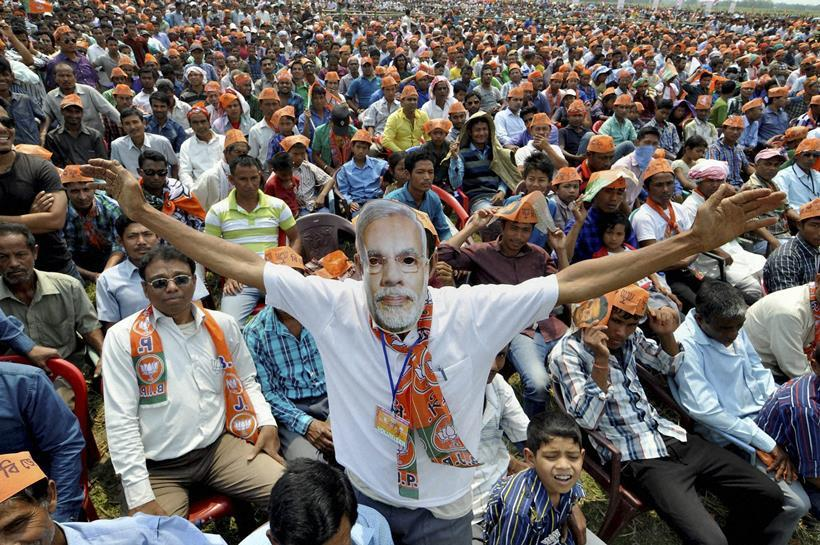 Majuli: A supporter wears a mask of Narendra Modi during his election rally at Majuli in Jorhat district of Assam on Saturday. Credit: PTI