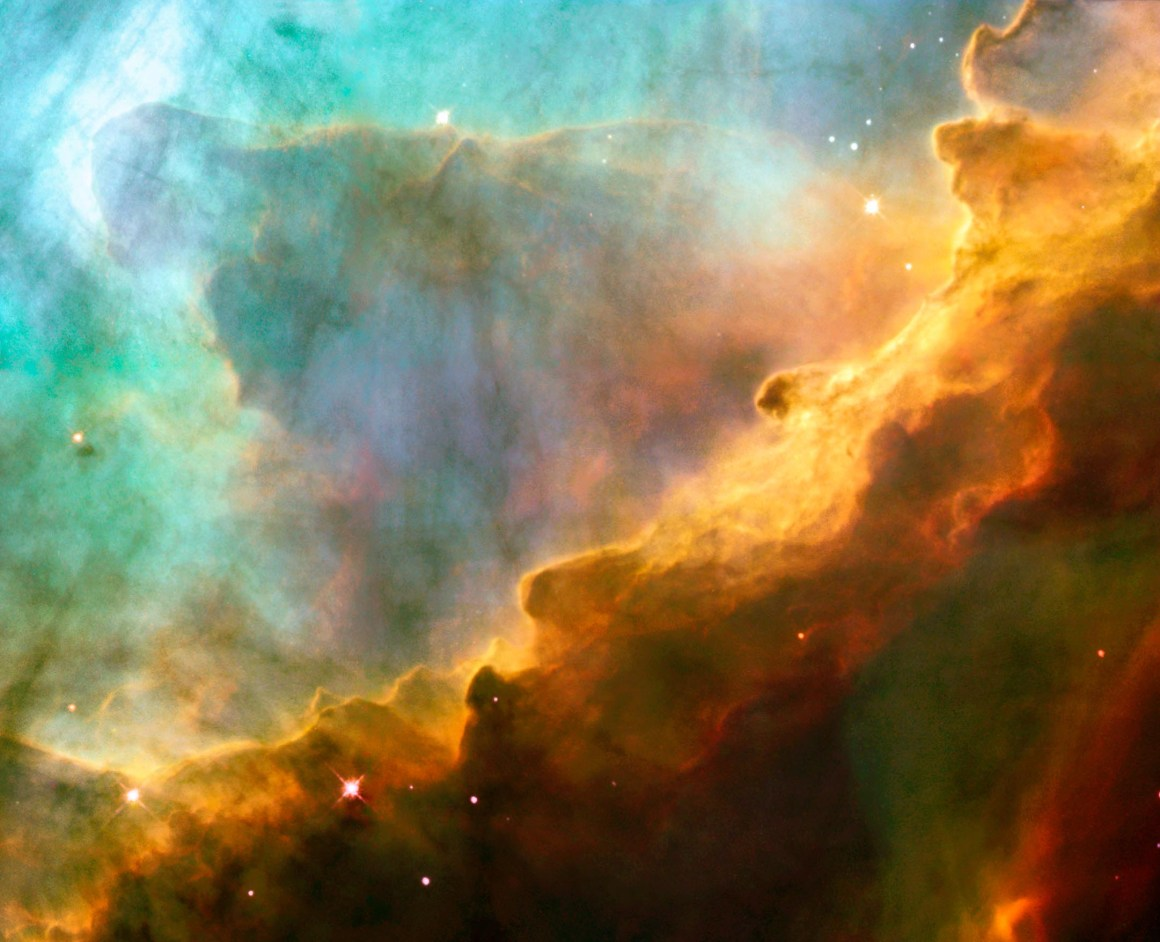 Resembling the fury of a raging sea, this image actually shows a bubbly ocean of glowing hydrogen gas and small amounts of other elements such as oxygen and sulphur. The photograph captures a small region within the Omega Nebula, located about 5,500 light-years away in the constellation Sagittarius. The wave-like patterns of gas have been sculpted and illuminated by a torrent of ultraviolet radiation from young, massive stars, which lie outside the picture to the upper left. Caption and credit: NASA, ESA and J. Hester (ASU)