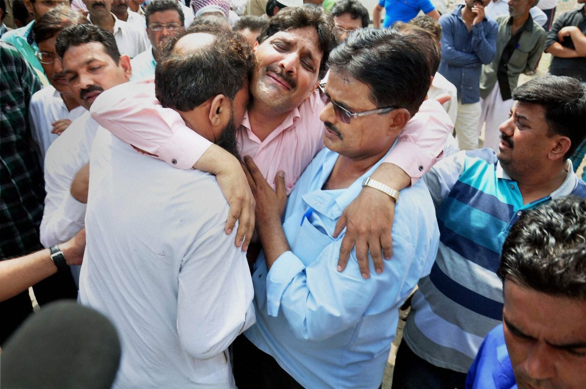 Relatives of NIA officer Mohammed Tanzeel who was killed by unidentified assailants in Bijnor last week, mourn outside the building where Tanzeel's post-mortem was conducted, in Moradabad on Sunday. Credit: PTI