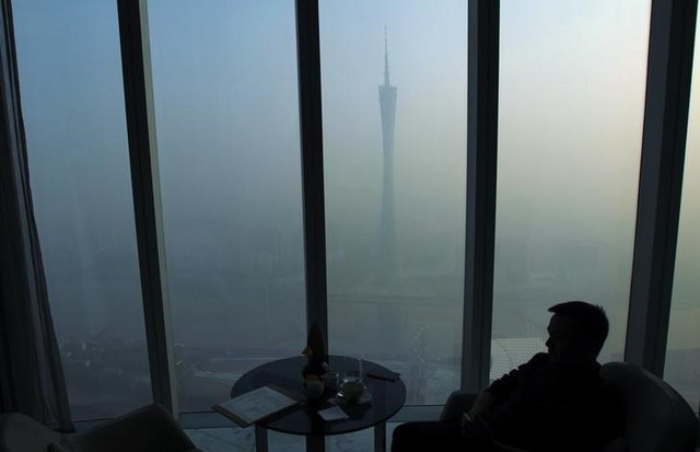 A man sits next to a window of a restaurant on the 70th floor of a skyscraper as the Guangzhou TV Tower is seen through thick hazy at the central business district in Guangzhou, Guangdong province February 17, 2014. Credit: Reuters/Alex Lee/Files