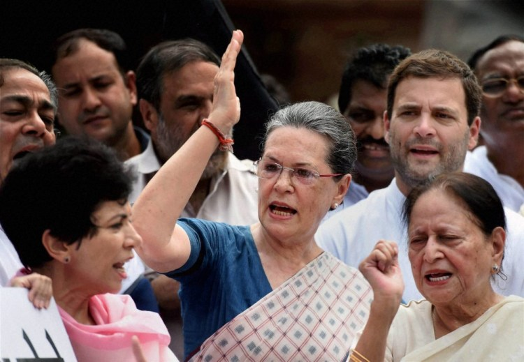 Congress president Sonia Gandhi, party vice president Rahul Gandhi and party leaders shout slogans outside parliament . Credit: PTI
