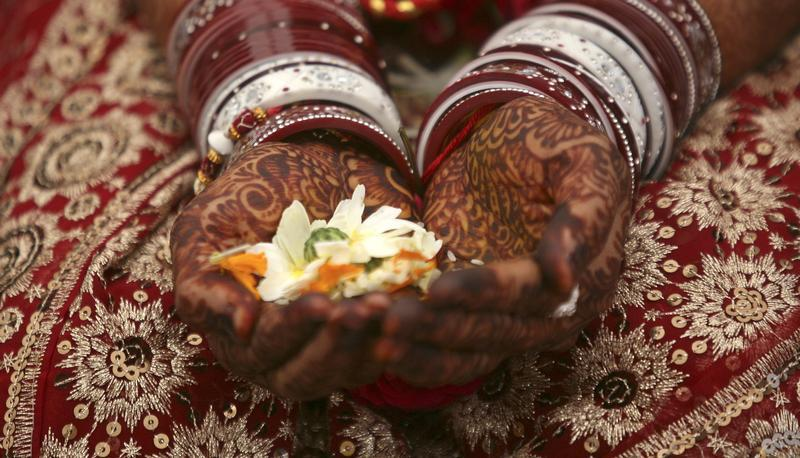 A bride holds flowers in her hands decorated with henna. Credit: Reuters/Amit Dave.