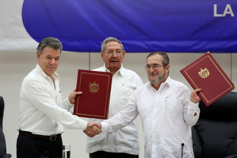 Cuba's President Raul Castro (C), Colombia's President Juan Manuel Santos (L) and FARC rebel leader Rodrigo Londono, better known by his nom de guerre Timochenko, react after signing a historic ceasefire deal between the Colombian government and FARC rebels in Havana, Cuba, June 23, 2016. Credit: Reuters/Alexandre Meneghini