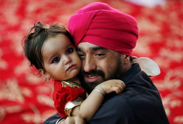 An Afghan Sikh holds his child inside a Gurudwara, or a Sikh temple, during a religious ceremony in Kabul, Afghanistan June 8, 2016. Credit: Reuters/Mohammad Ismail