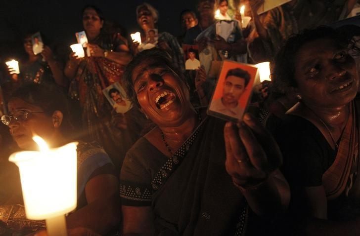 A Tamil woman cries as she holds up an image of her family member who disappeared during the civil war with the LTTE)at a vigil to commemorate the international day of the disappeared in Colombo August 30, 2013. Credit: Reuters/Dinuka Liyanawatte/Files