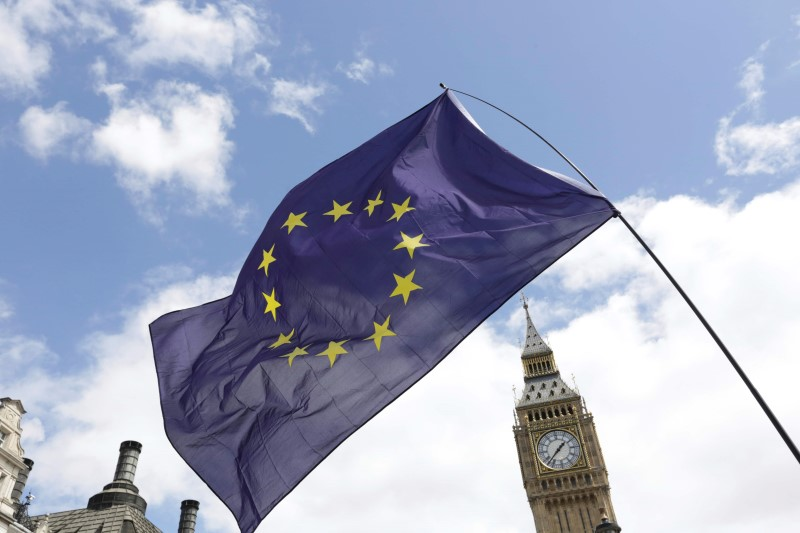 A European Union flag is held in front of the Big Ben clock tower in Parliament Square during a 'March for Europe' demonstration against Britain's decision to leave the European Union, central London, Britain July 2, 2016. Credit: REUTERS/Paul Hackett