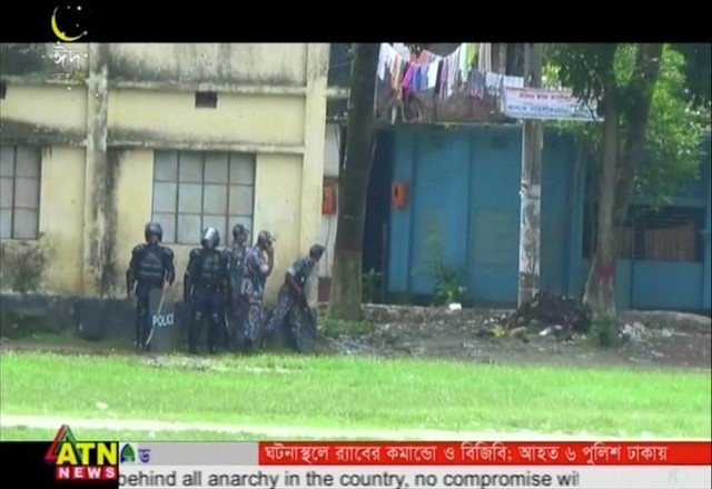 Police gather at a building near the attack site where militants attacked Bangladeshi police guarding an Eid festival in Kishoreganj town in this still frame taken from video July 7, 2016. Courtesy of ATN News /via Reuters TV