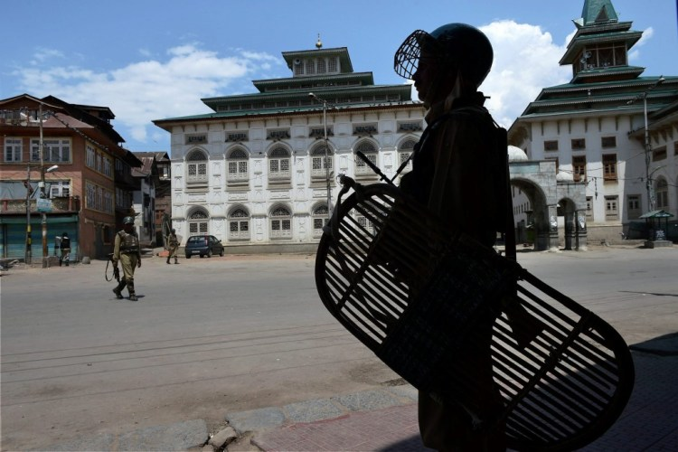 CRPF jawans stand guard during curfew in Srinagar. Credit: PTI Photo by S. Irfan