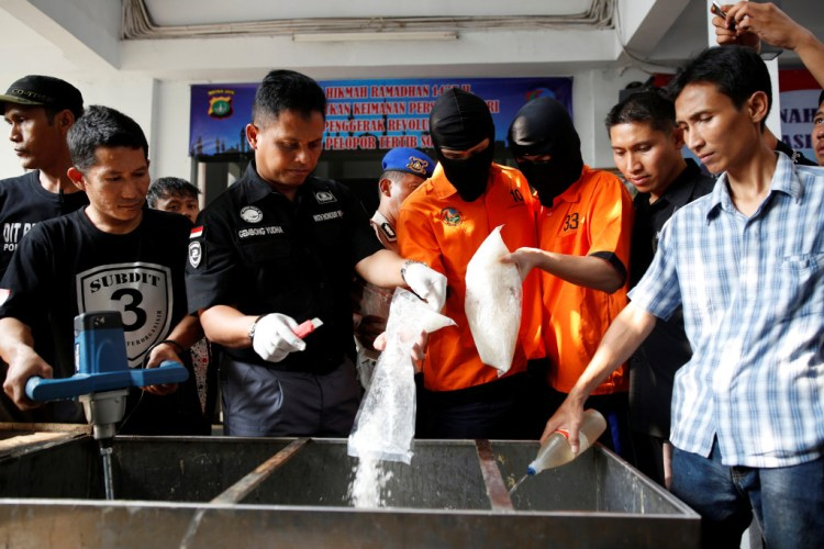 Recently arrested drug trafficking suspects are forced to take part in the destruction of illegal narcotics at police headquarters in Jakarta, Indonesia July 21, 2016. Picture taken July 21, 2016. Credit: REUTERS/Darren Whiteside