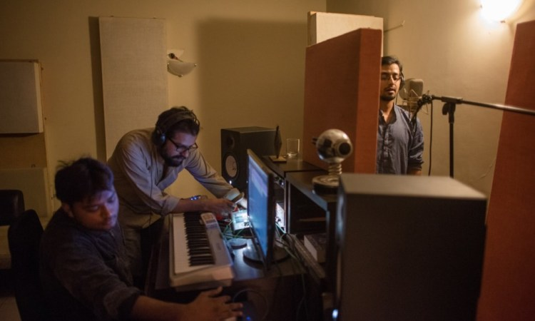 Ali Suhail records backup vocals for Ntasha Humera Ejaz's song at the studio of Omran Shafique (centre) of Mauj. Credit: Mohammad Ali, White Star/Herald