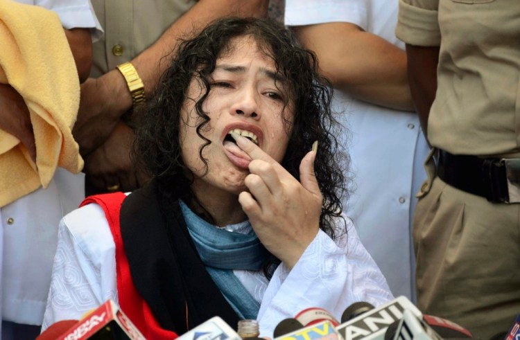 Irom Sharmila licks honey from her hand to break her fast during a press conference in Imphal on Tuesday. Sharmila ended her fast after nearly 16 years demanding repeal of the Armed Forces (Special Powers) Act. Credit: PTI