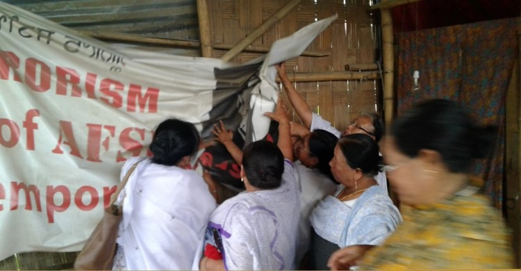Meira Paibi women tearing down posters marking end of Save Sharmila Campaign. Credit: Thingnam Anjulika Samom