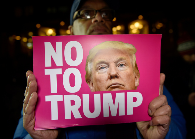 A man holds a placard at an anti-racism protest against US president-elect Donald Trump outside of the US Embassy in London, Britain, November 9, 2016. Credit: Reuters/Hannah McKay