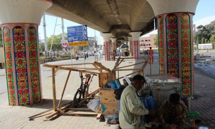 A man paints flower motifs beneath the Jinnah Hospital Flyover in Karachi for IAK. Credit: Annie Ali Khan/Herald