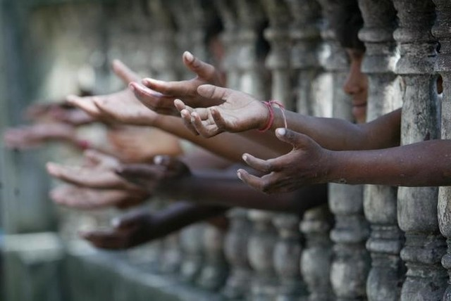 Homeless children reach out from behind a fence as they wait to collect free clothes at a local charity in Siliguri September 27, 2006. Credit: Rupak De Chowdhuri/Reuters/Files