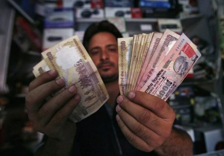 A shopkeeper poses for a picture as he counts rupees at his shop in Jammu. Credit: Reuters/Files