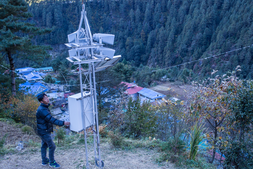 Nang thume Sherpa, member of Task Force for Glacial Lake Outburst Flood risk reduction shows the early warning system intslled in Fakding Village Solukhumbu, District Nepal. The early warning sytem will get autmated warning message from Automated Hydromet Sensor installed in Imja Glacial Lake.