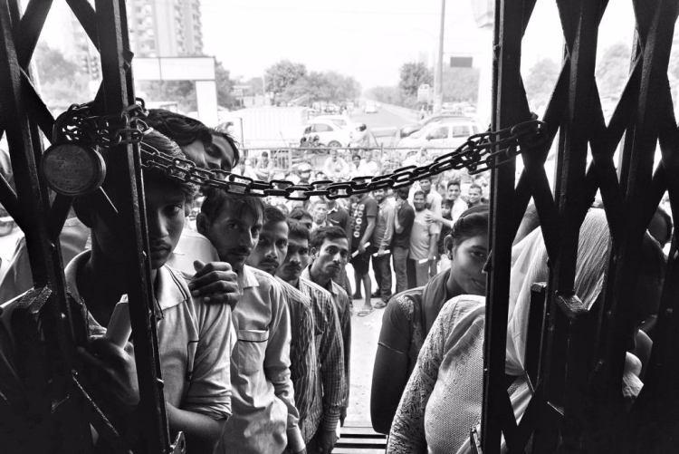 People queue outside a bank. Credit: Shome Basu