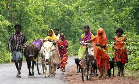 A family walks on a state highway at Pirakata near Lalgarh, some 165 km (102 miles) west of Kolkata in this June 20, 2009 file photo. Credit: Jayanta Shaw/Reuters
