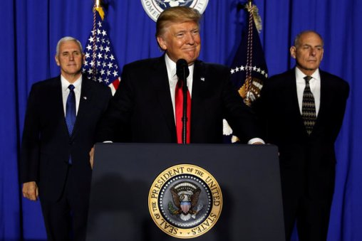 U.S. President Donald Trump (C), flanked by Vice President Mike Pence (L) and Homeland Security Secretary John Kelly (R), takes the stage to deliver remarks at Homeland Security headquarters in Washington, U.S., January 25, 2017. REUTERS/Jonathan Ernst