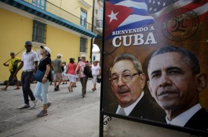 "Tourists pass by images of US President Barack Obama and Cuban President Raul Castro in a banner that reads ""Welcome to Cuba"" at the entrance of a restaurant in downtown Havana, March 17, 2016. Credit: Reuters"