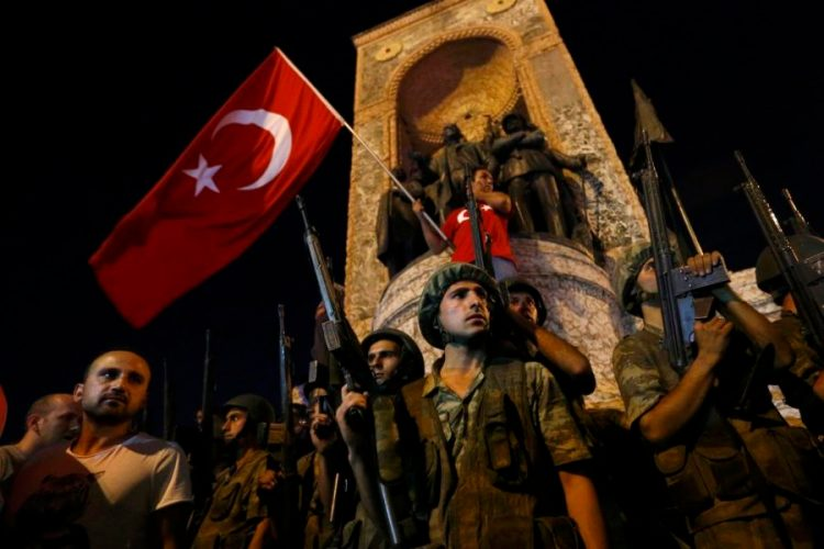 Turkish military stand guard near the the Taksim Square as people wave with Turkish flags in Istanbul, Turkey, July 16, 2016. Murad Sezer/Reuters/Files