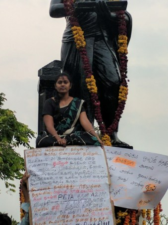 The woman in the black saree sitting on the statue.