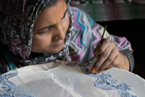 A woman practices sewing lace and sequins on a hijab in Shaheen Bagh. She plans to eventually sell crafts for an income. Credit: Meagan Clark