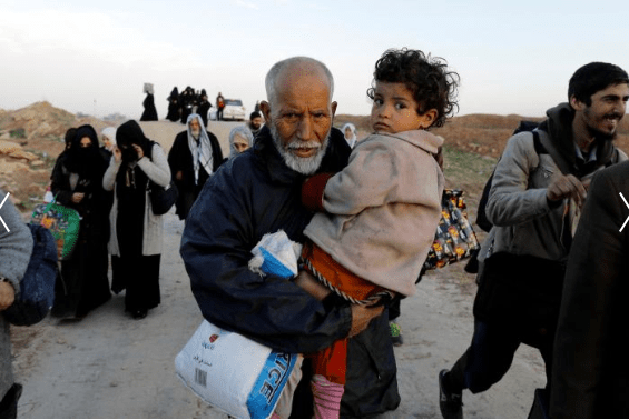 A displaced Iraqi man carries his granddaughter while fleeing his home, as Iraqi forces battle with Islamic State militants, in western Mosul, Iraq March 8, 2017. Credit: Zohra Bensemra/Reuters